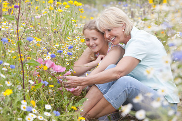 Grandmother and granddaughter looking at blossoms in field of wildflowers