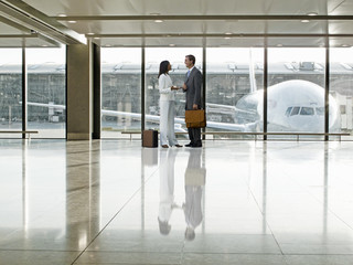Business people talking together in airport terminal