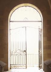 Open ornate iron gate in arched doorway