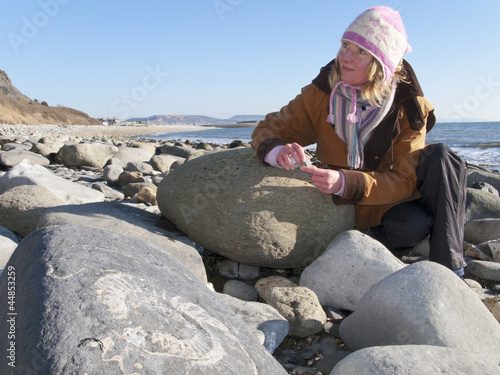 Woman looking at fossil in rock on ocean beach in winter