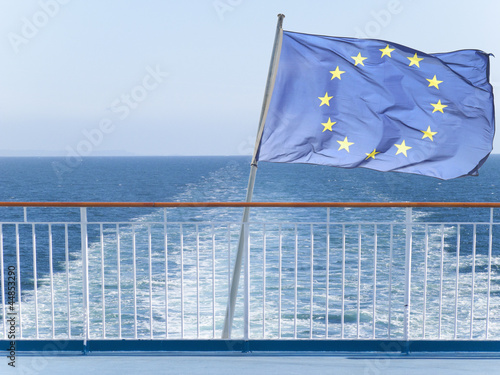 European Union flag on railing of ship with ocean water in background
