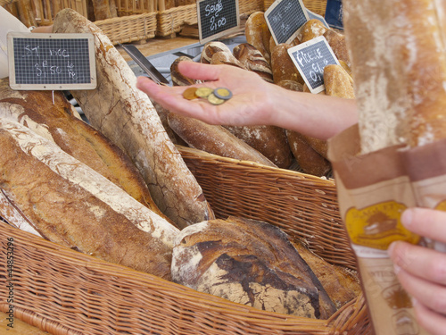 Woman holding coins buying rustic loaf of bread from market
