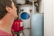 Plumber looking at central heating boiler
