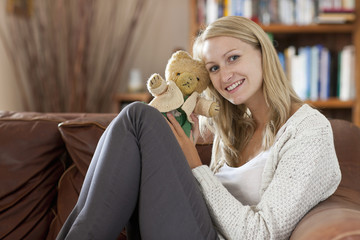 Woman sitting on sofa holding small teddy bear