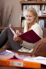 Woman sitting on sofa with books studying