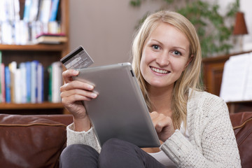 Woman sitting on sofa using credit card to shop online with digital tablet