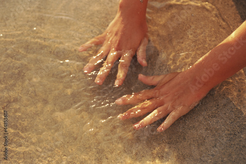 Close up of hands in ocean water at beach