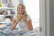 Portrait of smiling young woman in pajamas drinking coffee in bed