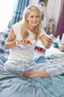 Young woman in pajamas eating cereal and holding remote control in bed