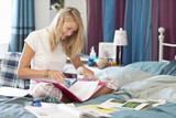 Smiling young woman in pajamas doing homework in bed