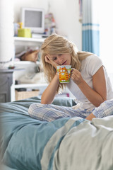 Woman with head in hands sitting on bed with coffee cup