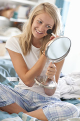 Smiling young woman in pajamas applying makeup with brush in small mirror