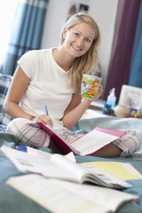 Portrait of smiling young woman in pajamas drinking coffee and doing homework in bed