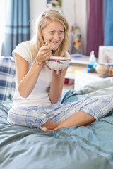 Smiling young woman in pajamas eating cereal in bed
