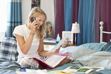 Smiling young woman in pajamas talking on cell phone and doing homework in bed