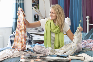 Young woman looking at clothes in bed