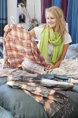 Young woman looking at shirt in bed