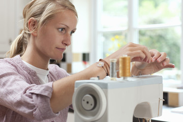 Young woman adjusting thread on sewing machine