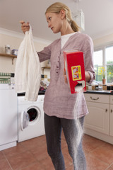 Young woman holding shirt and spilling detergent in laundry room