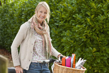 Portrait of smiling young woman with bicycle and textbooks in basket