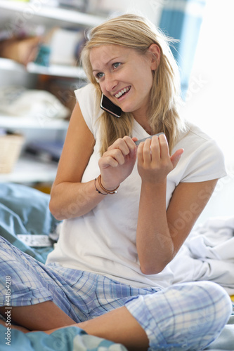 Smiling young woman in pajamas talking on cell phone and filing fingernails