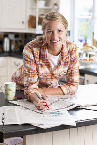 Portrait of smiling young woman circling classified ad in newspaper