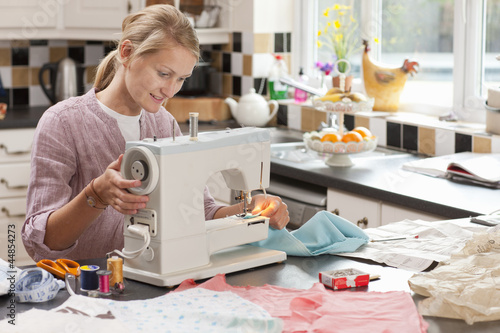 Young woman using sewing machine