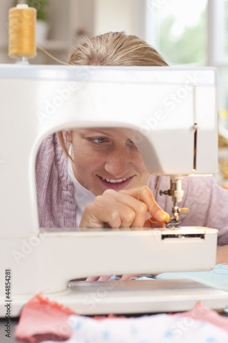 Smiling young woman adjusting thread on sewing machine