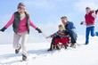 Happy family sledding down snowy hill