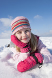 Close up portrait of smiling girl laying in snow