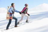 Couple with sled holding hands and walking up snowy hill