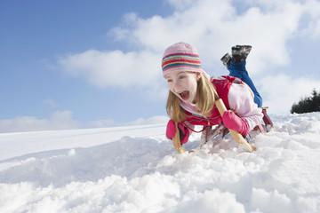Enthusiastic girl sledding down snowy hill