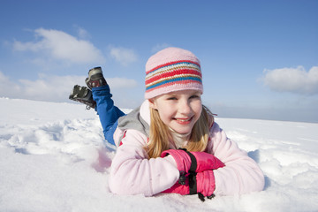 Portrait of smiling girl laying in snow