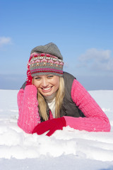 Portrait of smiling woman laying in snow