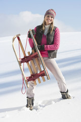 Portrait of smiling young woman holding sled in snow