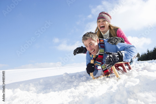 Happy couple sledding down snowy hill