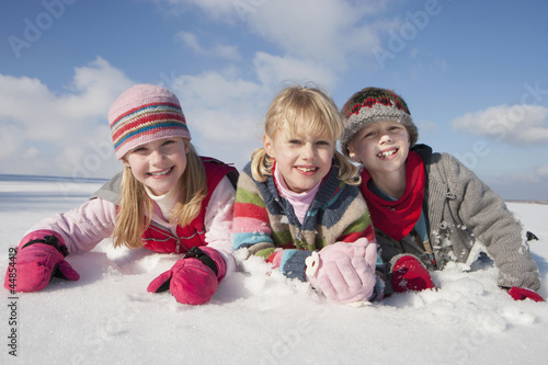 Portrait of smiling boy and girls laying in snow