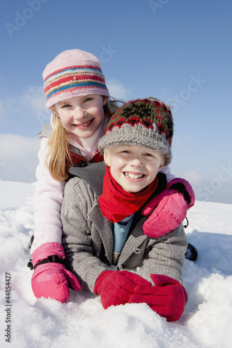 Portrait of smiling boy and girl laying in snow