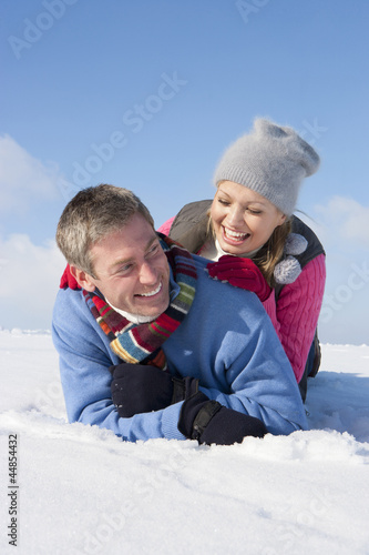 Smiling couple laying in snow