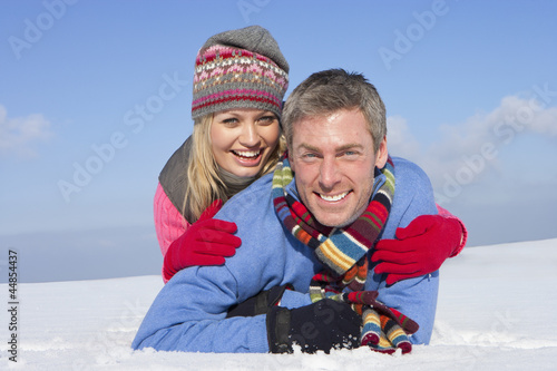 Portrait of smiling couple hugging and laying in snow