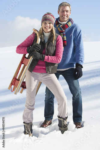 Portrait of smiling couple with sled in snow