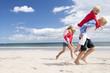 Boy and girls piggybacking on sunny beach
