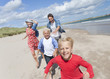 Happy family running on sunny beach