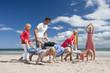 Family playing wheelbarrow race on sunny beach