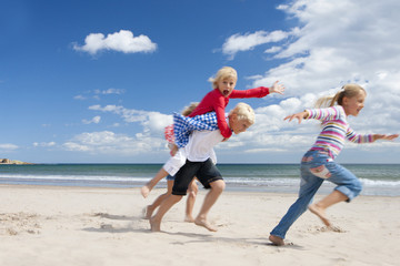 Boy and girls running on sunny beach