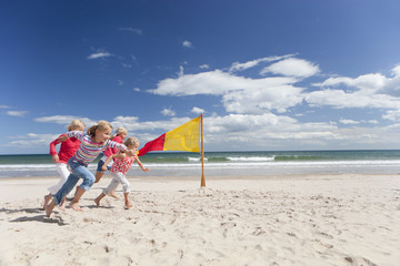 Kids running on sunny beach