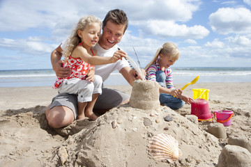 Father and daughters making sandcastle on sunny beach