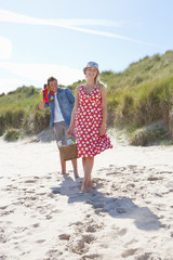 Smiling couple with picnic basket on beach