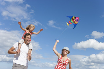 Father carrying daughter on shoulders and mother flying kite