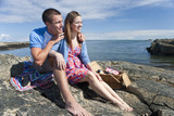 Smiling couple with picnic basket sitting on rocks along ocean